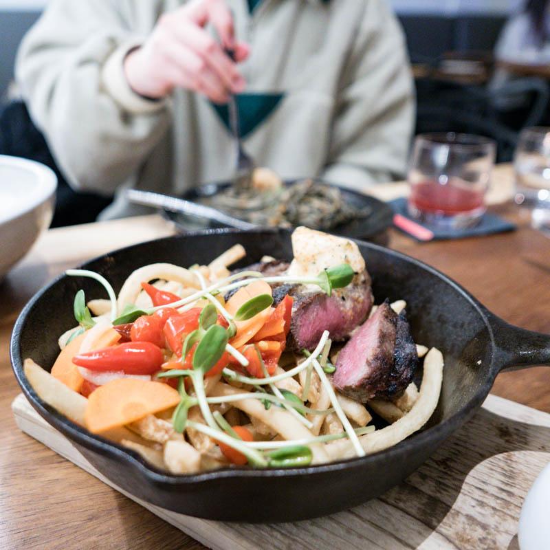 Grilled 7oz sterling flat iron steak, miso gravy, togarashi compound butter, frites, spicy vegetable